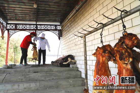 店主艾山江·努尔买买提和员工将烤好的羊提出馕坑。
