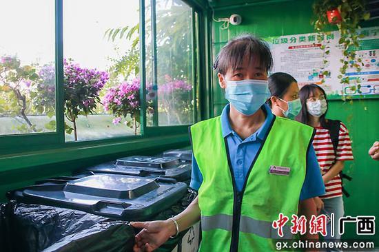 图为盛天茗城保洁人员介绍该小区的垃圾定时定点分类投放屋。班秀  摄