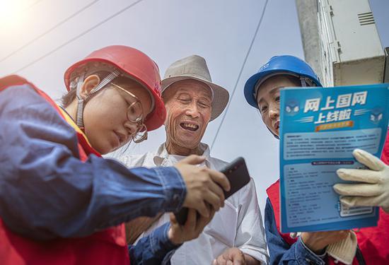 国网乌鲁木齐供电公司党员服务队员主动走访辖区客户,介绍网上缴费方式。王晋魁 摄