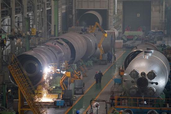 People work in a workshop of Harbin Boiler Company Limited in Harbin, northeast China's Heilongjiang Province, Feb. 10, 2020. (Xinhua/Wang Jianwei)