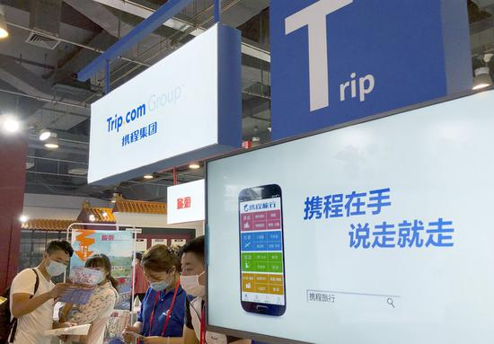 Visitors check information brochures at the Trip.com Group stand during an expo in Beijing. (Photo/China Daily)
